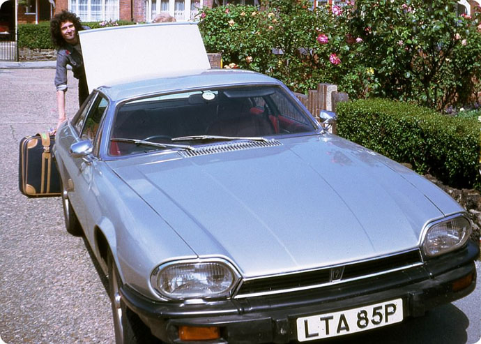 Brian loading suitcase in new Jaguar car